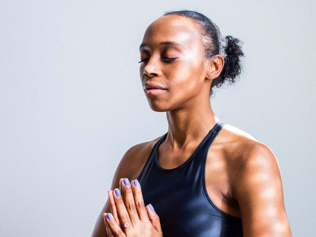 A woman does a calming yoga pose against grey background.