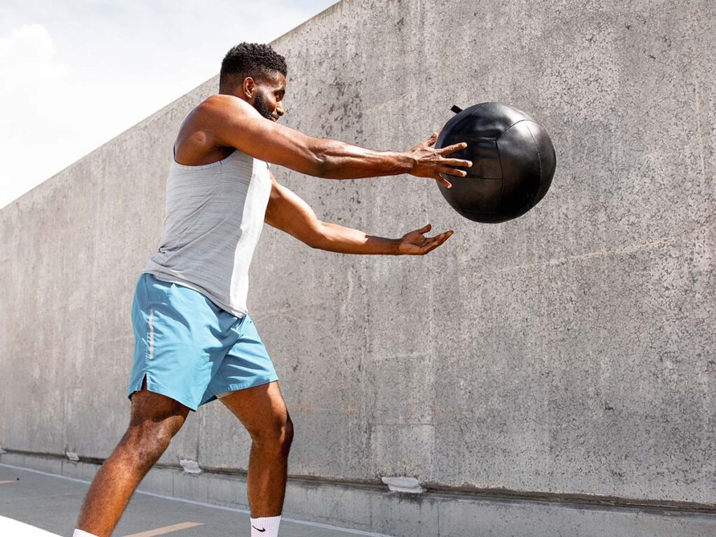 A man exercises with a black weight ball outside.